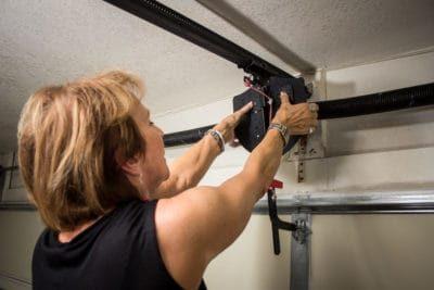 Women installing garage shield