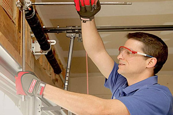 man adjusting garage door cables inside a garage