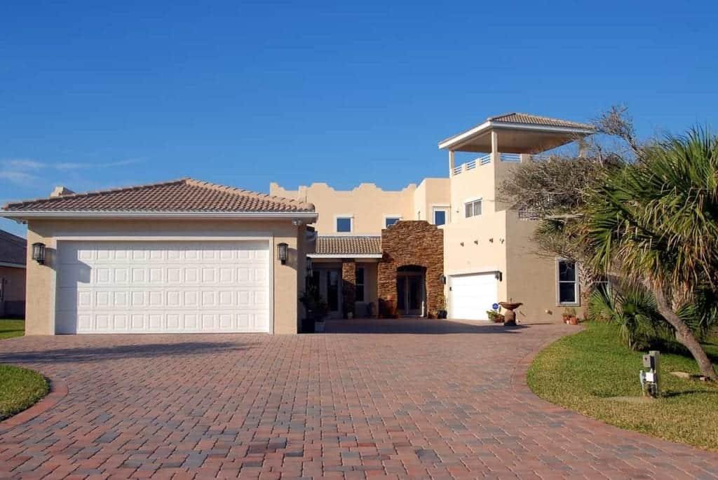 brick driveway with white double car garage door