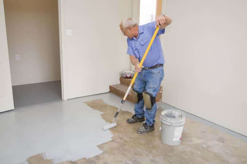 a man painting his garage floor